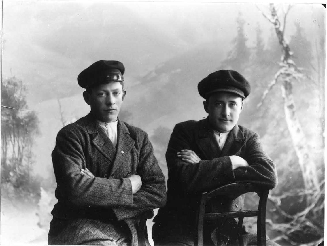 Gruppbild med två unga män i grov kavaj och keps på huvudet. Mannen till vänster är Algot Lätt från Bunnström, Gränna socken.