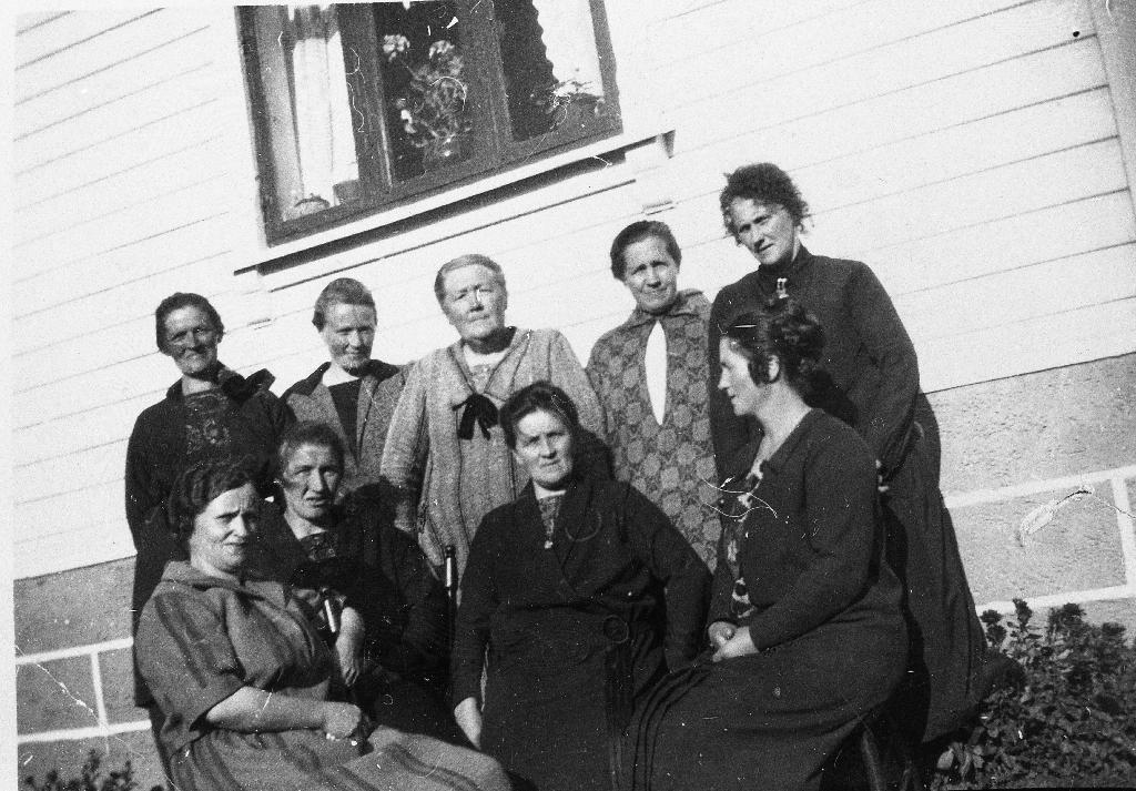 I hagen framfor huset til Ivar Løge. Bak frå v. Lisa Line, fru Kverneland, Ane Fjogstad, Guri Årrestad, Berta Øgård. Framme f. v. Klara Kindervåg, fru Skjæveland, Borghild Løge og Tomine Siqveland.