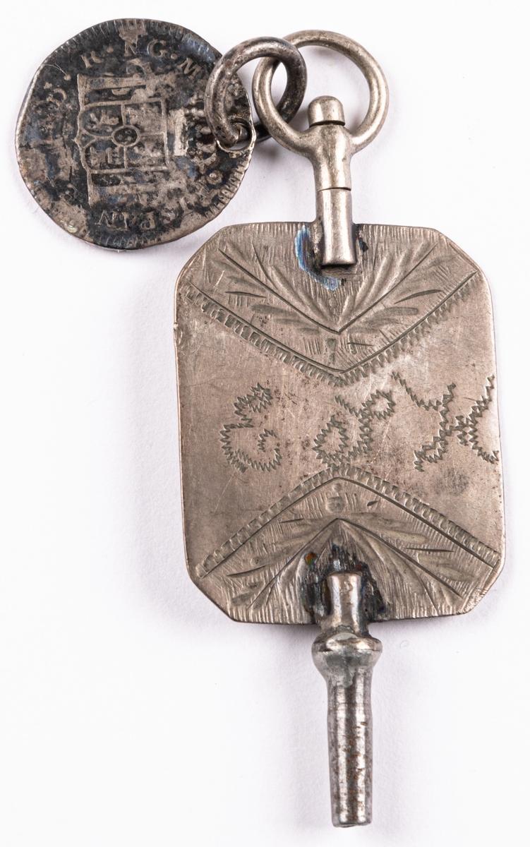 Urnyckel av silver, med vidhängande spanskt-colombianskt mynt (8 reales) från 1809, också i silver. Nyckeln märkt E.S.H.