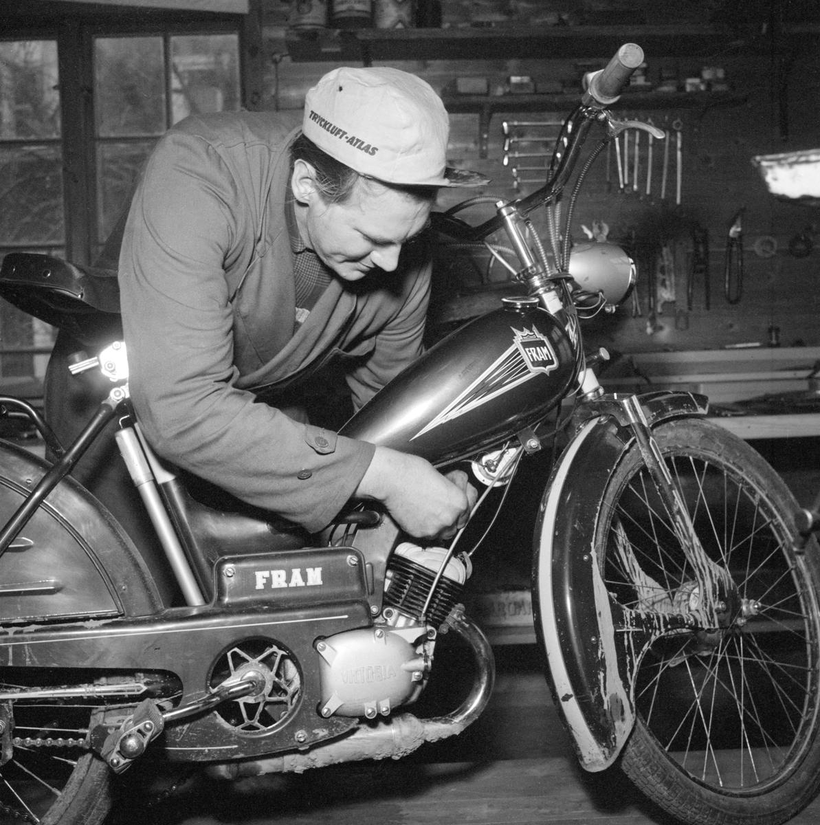 Reparatör Gösta Månsson skruvar på en svensktillverkad Fram modell 40, med den för typen tillhörande, tyska motorn Victoria MS50. Det tycks vara kontroll av tändstiftets funktion och så långt är det till synes ett alldagligt motiv. Det som gör scenen märkvärdig är att Gösta var synskadad men ändå lyckades driva sitt företag med nödtvunget småspill trots sin funktionsnedsättning. Från slutet av 1950-talet till sin pension drev han verkstad på Skänningevägen i Borensberg och många är de ortsbor som minns hans flinkhet. Född 1924 kom han långt efter tiden för bilden att gifta sig med en kvinna vars gemensamma försyn förde dem till Kristinehamn. Han avled där 2011, kort före han blivit änkling.