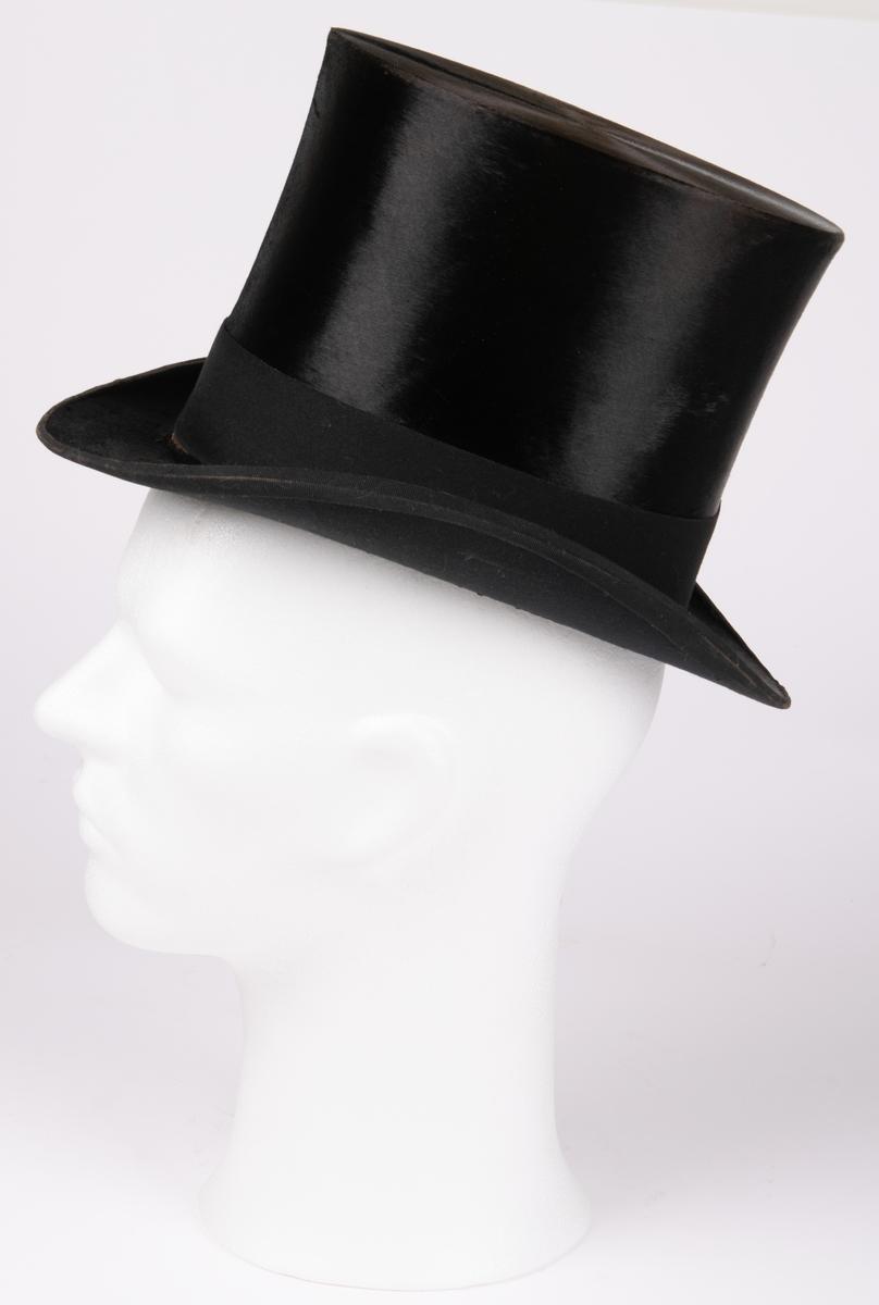 Hög hatt med kraftigt uppsvängda brätten, märkt B.L. ink. hos firma J.W. Haglund, Gefle. Tillhörande hattask.