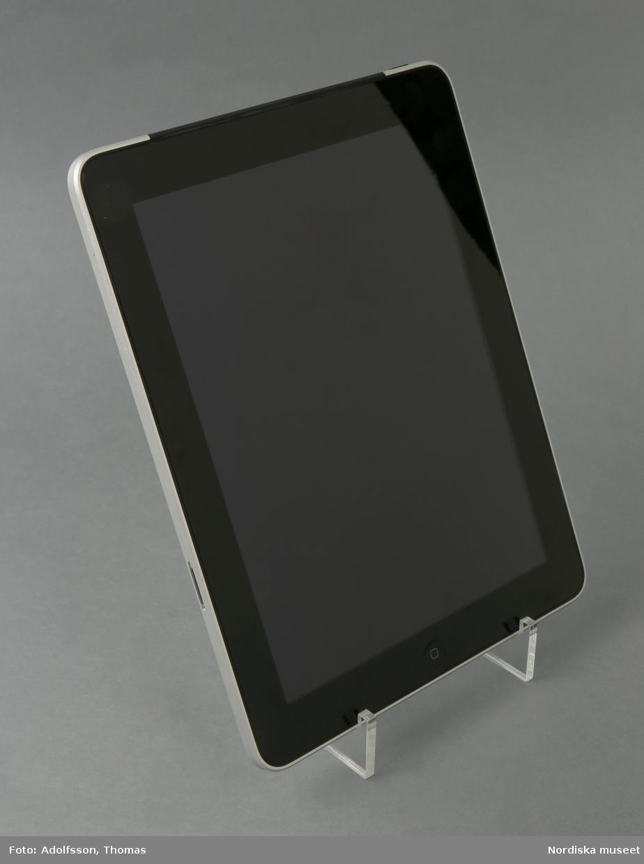 """iPad 64 GB. En platt beröringskänslig glasskärm . I skärmen syns en svart bred ram infärgad i glaset, Denna ram inramar bildytan på skärmen. På skärmens nedre del finns en rund grop (ca 1 cm diam) vilken är iPadens hemknapp. iPadens på/av-knapp är placerad på höger sidas övre kant. Utmed högra långsidans kant finns ljudets på/av-knapp följd av volumknappen. På den nedre kanten finns dels högtalarna och dels uttag för uppladdning av IPadens batteri.    Baksidan på IPaden är täckt av ett aluminiumhölje som döljer och skyddar tekniken. När iPaden startar tänds skärmens bildyta upp med LED-ljus. Därefter är det bara att börja """"surfa"""".  /Cecilia Wallquist 2019-01-30"""