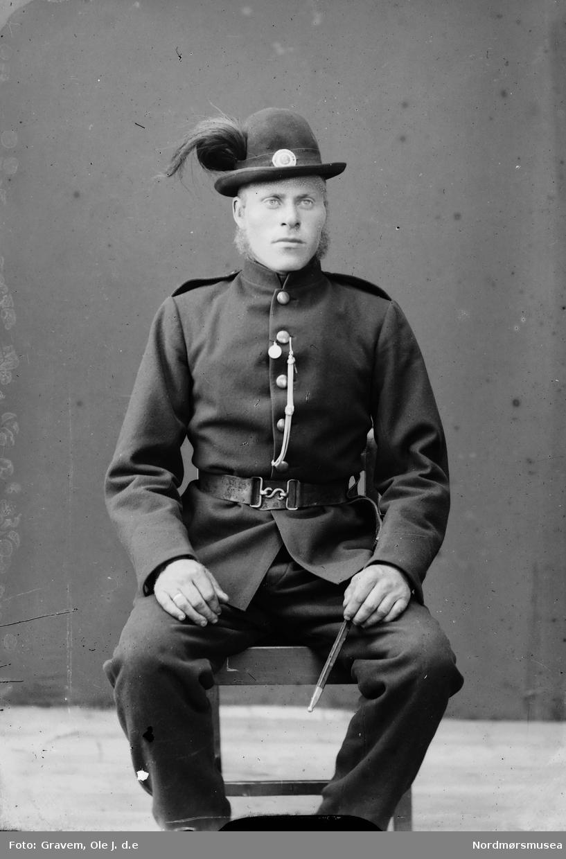 Sittende mann i uniform.