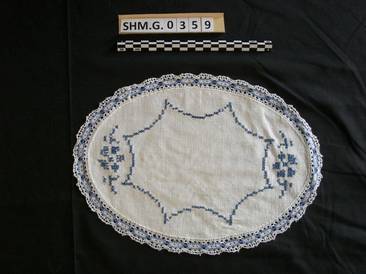 Liten oval brikke i hvit lin med korsstingsbroderi i blått. Maskinblonde hvit og blått.
