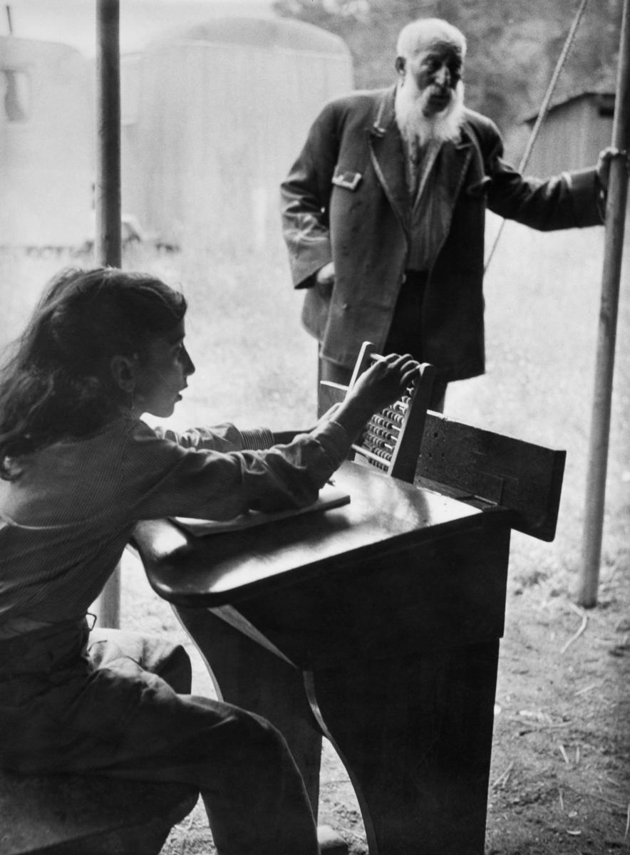 """Trots att Sverige haft skolplikt sedan 1842 har inte alla barn haft rätt att gå i skolan. Redan 1933 skrev Johan Dimitri Taikon till skolöverstyrelsen och bad om skolundervisning för romska barn. Först tio år senare blev han hörsammad, då han tillsammans med den frikyrkligt engagerade Otto Sundberg blev beviljad 1500 kronor för att starta en """"försöksskola"""". Denna verksamhet kom senare att drivas för Stiftelsen Svensk Zigenarmission, som drev sommarskola för romska elever under hela 1940- och 1950-talen. Både vuxna och barn gick då i skola. Först efter att alla romer fick bli bofasta år 1959 fick samtliga romska barn möjlighet att gå i skola året om. Bilden föreställer en av de elever som fick undervisning i Hägersten sommaren 1958."""