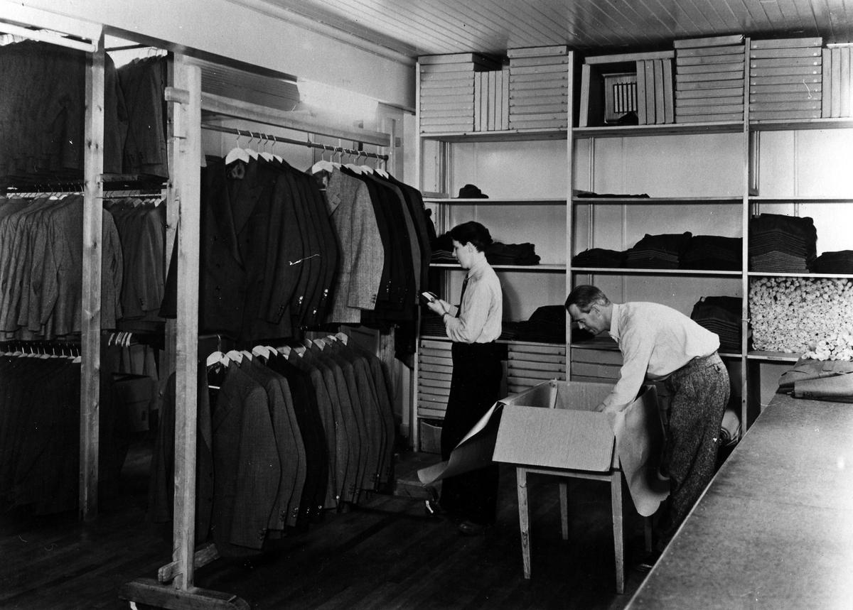Två män packar och inventerar kläder på Drabant AB:s färdiglager.