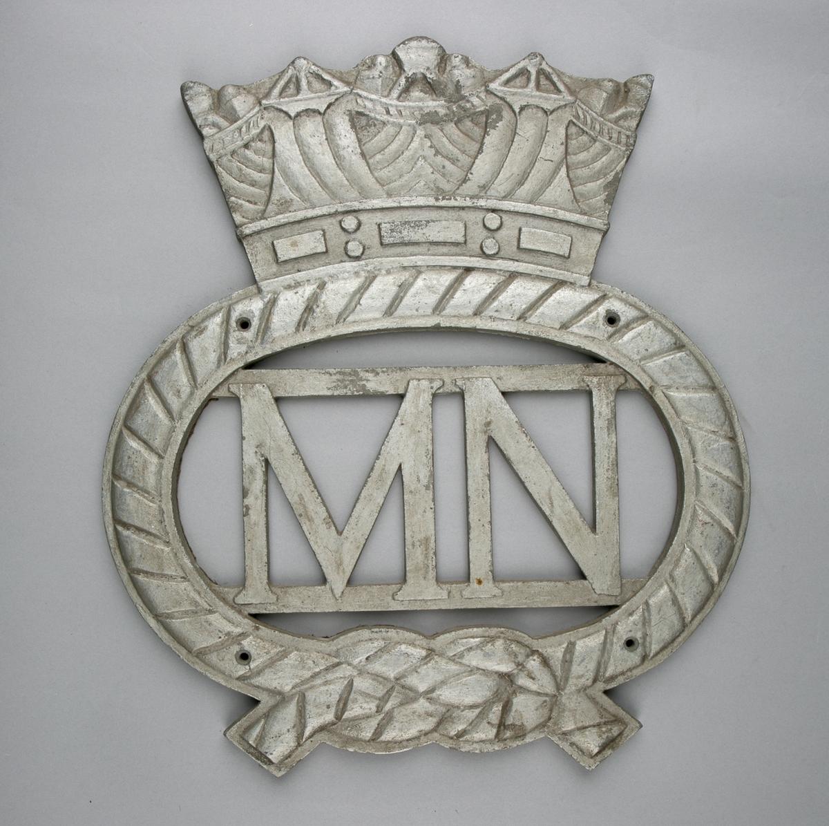 Ovalt emblem med krone. I senter bokstavene MN. Emblem ser ut som tau med båtsmannsknop.