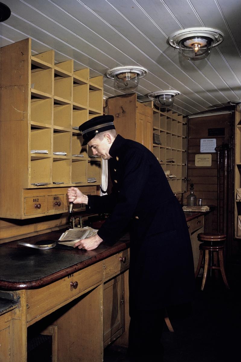 I en ålderdomlig järnvägspostkupé, i Järnvägsmuseum i Tomteboda, Solna, stämplar en postiljon avgående post. I den arrangerade situationen agerar fotobiträdet Gunnar Svensson, Postens Fotografer, i en uniform från Postmuseum.