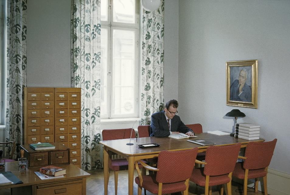Bild 33 i en serie av 38. Bibliotekets läsrum, med fönster mot Lilla Nygatan. Som besökare agerar museets vaktmästare postiljon Nils Svensson.