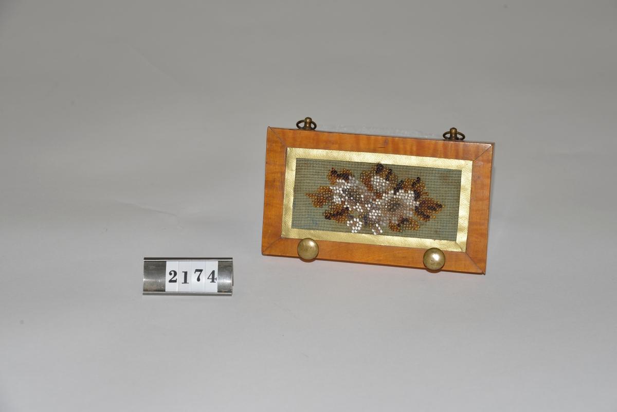 Handbroderad med pärlor, blommotiv. 2 st knoppar av mässing. Har tillhört givarens familj.