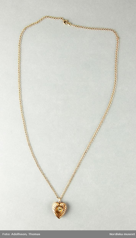 Halsband med a) berlock i hjärtform omgärdandes en kompass. Hjärtat är dekorerat med diagonala längsgående räfflor. b) Smal guldkedja i gulmetall.  /Cecilia Wallquist 2019-02-15