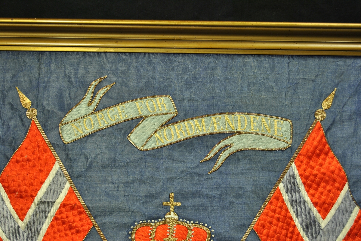 I midten er et skjold med løven fra Norges riksvåpen kompinert med Bergens kommunevåpen. På hver side står to løver på bakbeina med krone på. Krone også over skjoldet i midten. Et Norsk flagg på hver side. Banner med ordene Norge for Nordmændene på. Flora nederst.