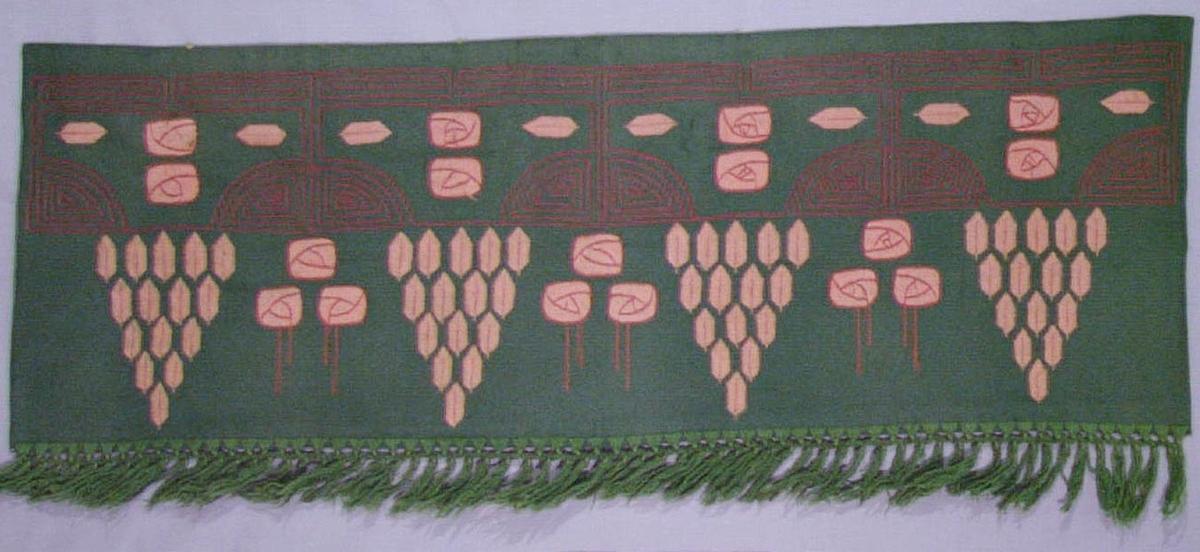 Gardinkappa av grönt ylletyg broderad med rosa och rött ullgarn i plattsöm och stjälksöm. Fodrad med grönt bomullstyg i satinbindning. Försedd med grön, flätad frans.