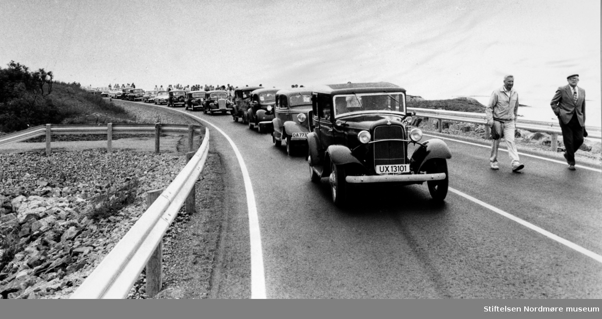 """Fra en veteranbiloppvisning på Atlanterhavsveien mellom Averøy og Eide i Møre og Romsdal. Atlanterhavsveien er en veistrekning på 8.274 meter. Anlegget består av åtte broer på til sammen 891 meter og går over holmer og skjær. Veien kostet 122 millioner i 1989 og var delvis bompengefinansiert. Anlegget ble åpnet 7. juli 1989 og bommen ble fjernet i juni 1999. Atlanterhavsveien er landets åttende best besøkte naturbaserte turistattraksjon (2004) med 283.500 besøkende. Veistrekningen er foreslått vernet i """"Nasjonal verneplan for veger, bruer og vegrelaterte kulturminner."""" (Kilde: Wikipedia Norge)."""