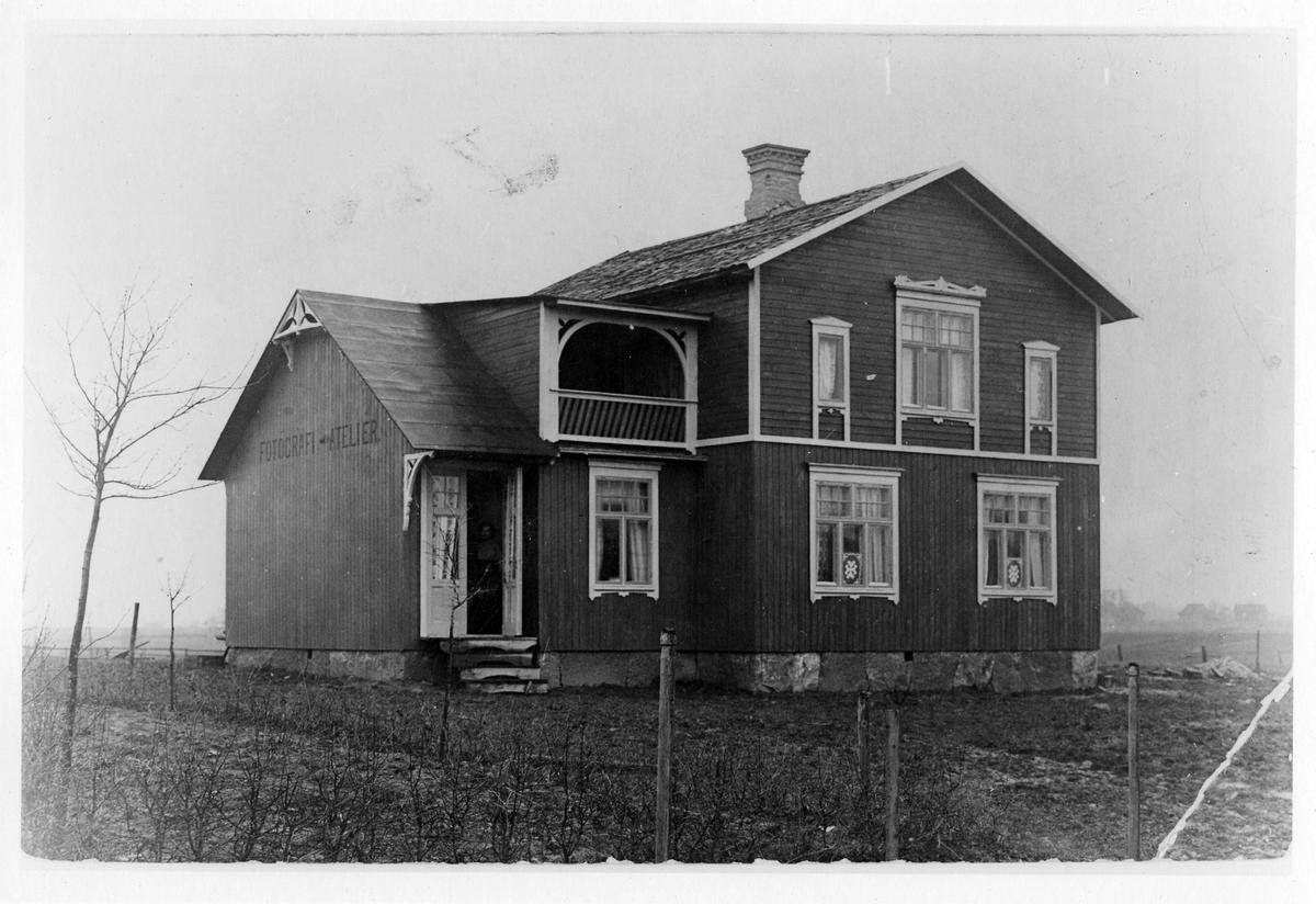 """Fotograf Westins fotoateljé och bostad i Sollebrunn. Trähus med två våningar och i dörröppningen skymtas, vad som ser ut att vara, en kvinna. På kortsidan av byggnaden står det """"FOTOGRAFI ATELIER"""""""