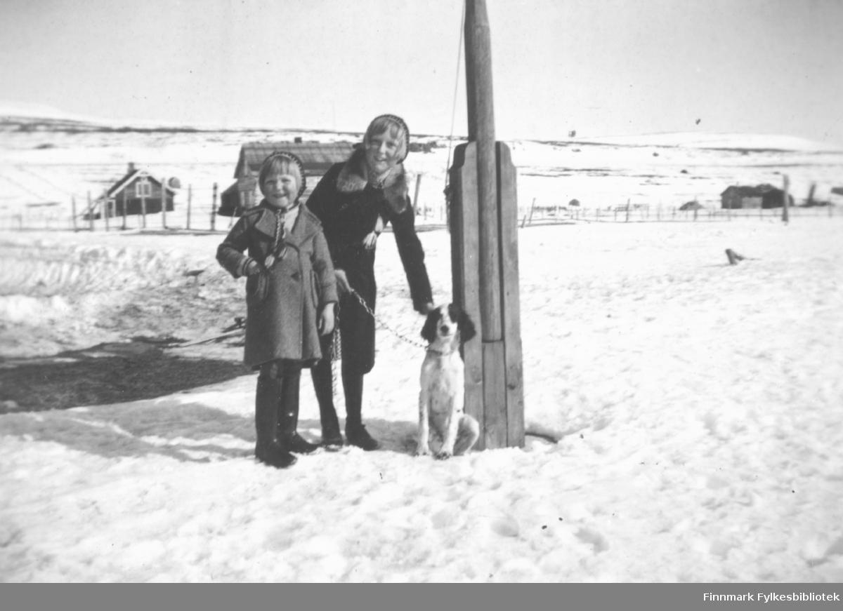 Ester, Ingrid og hunden Mona. 1939. Hunden er muligens en engelsk setter. Barna står oppstilt ved flaggstanga. Familiealbum tilhørende familien Klemetsen. Utlånt av Trygve Klemetsen. Periode: 1930-1960.