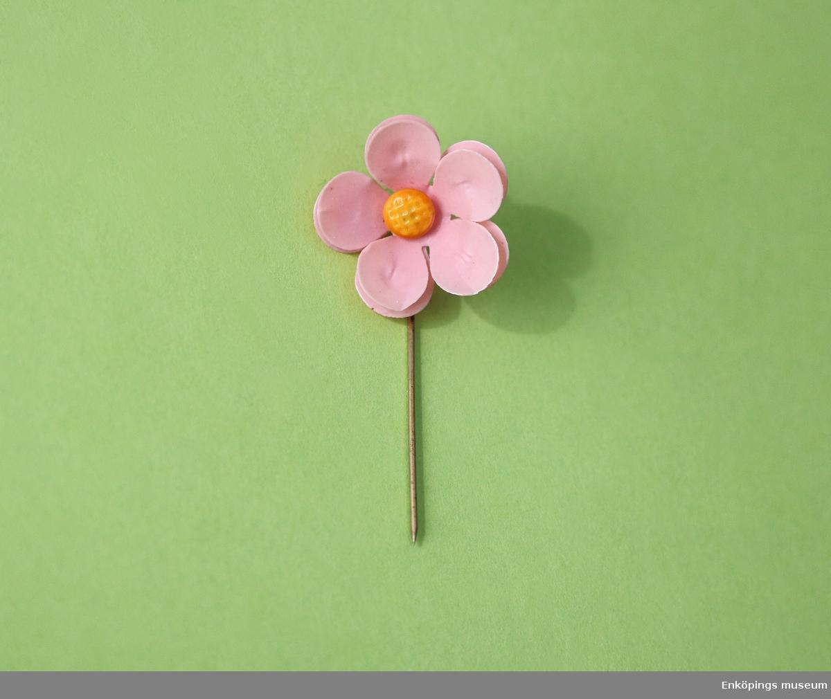 Majblomma från år 1911. Blomman är gjord av rosa celluloid och har fem blad i dubbla lager, totalt 10 blad och en gul mittknapp, även denna gjord av celluloid.  Det som håller blomman samman är en nål av mässing.