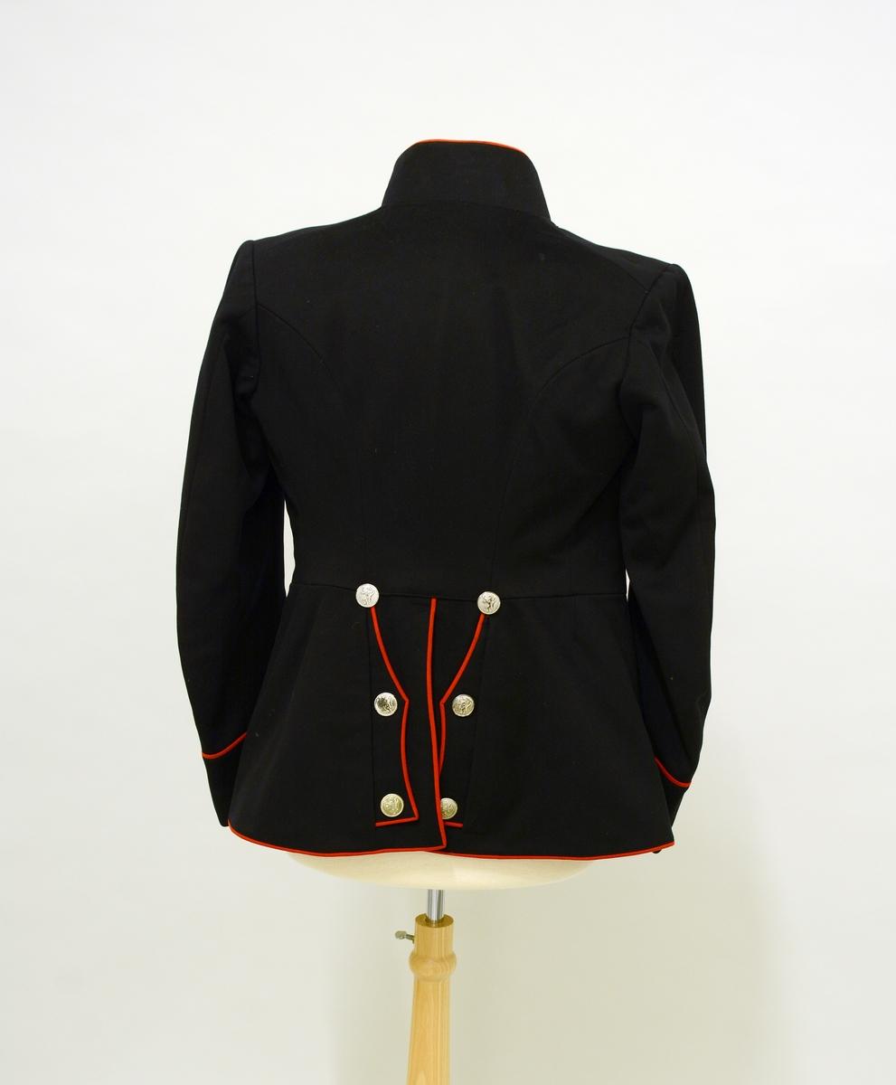 Uniformsjakke. Sort uniformsjakke i klede. Rød paspoil rundt hele formen. Ståkrave med distinksjoner, tre stjerner som er antageligvis kapeinsgrad. Distinksjonene på skuldrene er tatt av. Metallknapper med riksløven: 8 stk foran, 6 stk bak og 3 stk på hver arm. Innvendig fôret med rødt silkestoff.
