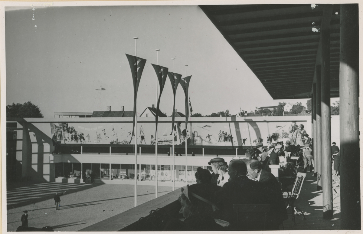 """Jubileumsutstillingen i Moss 1937 da Moss Handelsstand feiret sitt 50-års jubileum. Seks bilder.  Bilde 1-2: Åpningsdagen, Sandløkken på Skarmyren idrettsplass. Bilde fra samme setting, uten publikum, publ. i """"Moss som den var"""" (Jørgen Herman Vogt, 1970), s. 280.  Bilde 3-4: Konditoriet. B. 3 har bytårnet i bakgrunnen.  Bilde 5: Mot nord.  Bilde 6: Åpningen. Utstillingskomiteens formann, Helly Hansen holder åpningstalen."""