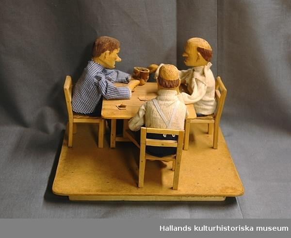 Tre män som sitter på varsin stol runt ett slagbord och spelar kort, en röker pipa, en bjuder på snus. Allt utskuret i trä. Skulpturen rörlig medelst tre spakar som sitter under den rektangulära masonitplattan på vilken allt är fastsatt. Männens kläder sydda av blått och vitt bomullstyg.