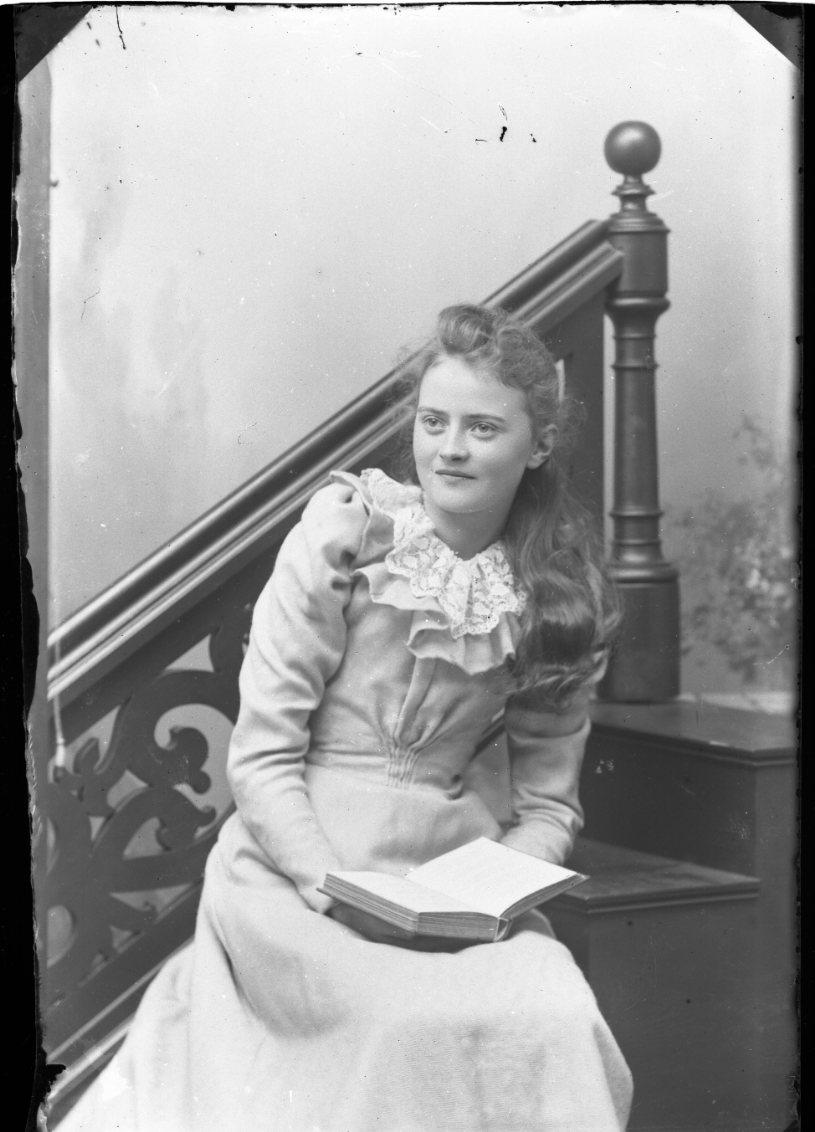 Porträtt av Ester Grönberg. Hon sitter i en trappa med en bok i knät.