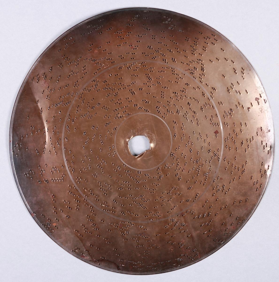 """Perfortert metalplate med pigger på underside. Programmert musikk for platespilledåse. 86-spor, Ø 30 cm. Drivsystem: Sentrumshull med kvadratisk """"satellithull"""" ved siden (7x5 mm).  Sentrumhull, diameter: 8 mm  Avstand mellom 10 spor: ca 13 mm. Avstand sentrumsaksling – første spor:  33,8 mm Total bredde spor:  110,4 mm"""