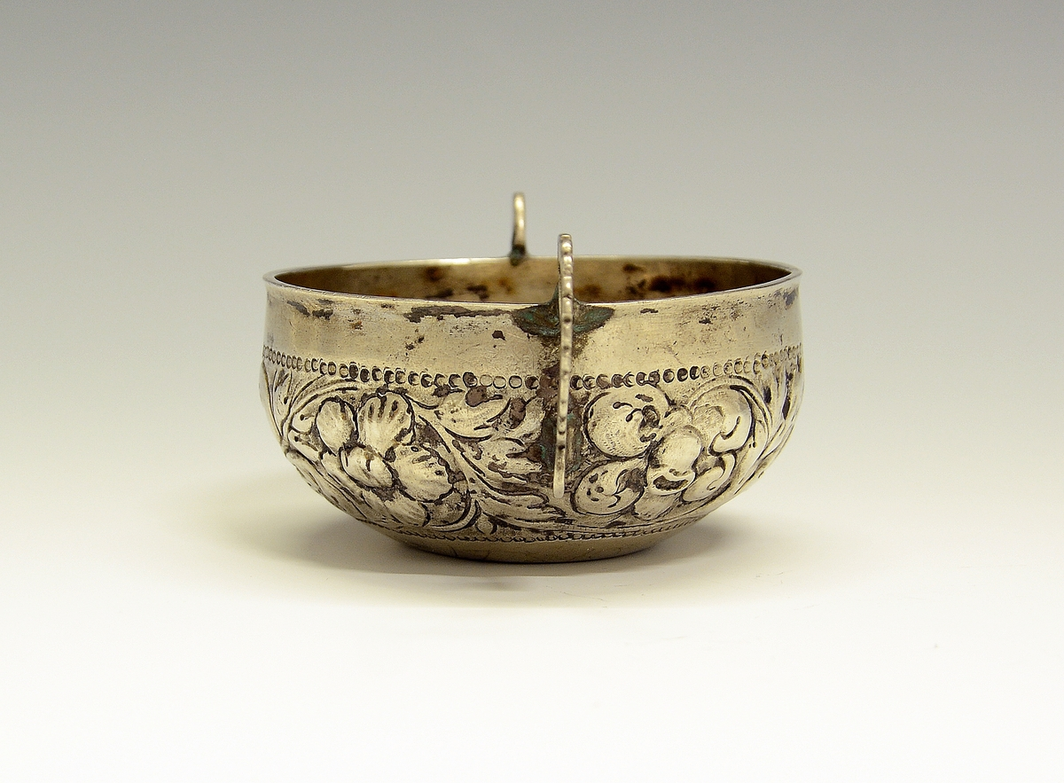 Øreskål. Fra protokollen: Sylvbolle med 2 hevlar (hanker). Ikring er drivi eit rankormanent. Sylvstempel under MNS 1709. (R. Berge) Mester Michel Nielsen, Øyestad.