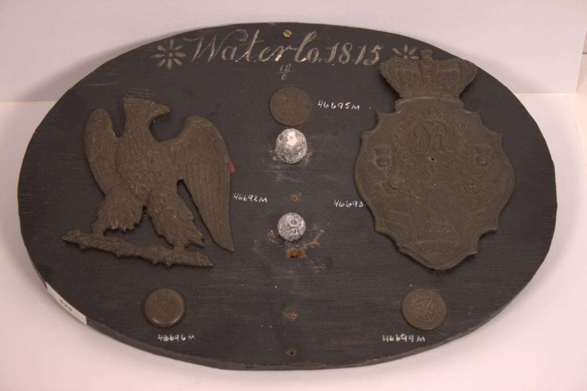 Fransk keiserørn uten krone fra 1815. Beskrivelse, se foto. Fremstillet i messing. På baksiden påloddet 4 ører. Keiserørnen skulle hatt krone over hodet. Dette bærer tydelig tegn på at kronen er brukket av. Sammen med en del andre gjenstander som er funnet på slagmarken ved Waterlo er denne gjenstand montert på en oval sortmalt treplate. På platen står i hvit maling: *Waterlo 1815* 18/6
