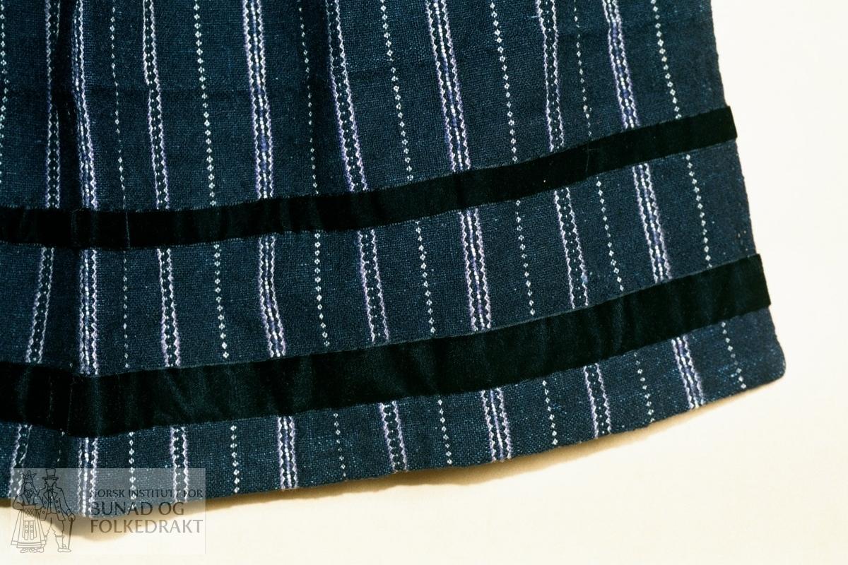 """""""Første eigar har fått dette forkleet hjå tanta si. Mest sansynleg er forkleet frå ca. 1850-åra"""".  Lerretsbinding i to mørke blåfarger. Mønsterstriper i kvitt og lilla. Bomull i renning, innslag i ull, bortsett fra det kvite - bomull. Linning av svart silkefløyelsband, 1,7 cm bredt. Foldelagt mot midten med syv folder på hver side av midt foran. Hemper til forkleband i hver side, men sekundært påsydd forkleband av svart kunstsilke. Metallknapp. Skoning nede av kvitt bomullslerret, ca. 2,6 - 3 cm bred. Svart fløyelsband, 2,5 cm bredt, påsatt ca. 3 cm fra nedrekanten. Svart fløyelsband, 1,6 cm bredt, påsatt ca. 10,5 cm fra nedrekanten. Trolig senere påsydd. Håndsydd.  Lengde linning:  ca. 27,5 cm. Bredde forkle:   ca. 63,5 cm. Høyde forkle:    ca. 84,5 cm."""