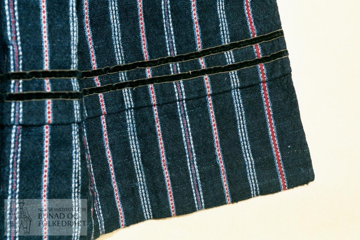 Lerretsbinding i to mørke blåfarger. Renning i bomull, innslag i ull, bortsett fra det kvite - bomull. Striper/mønsterborder i rødt + kvitt + lys blått, kvitt + lys blått. Rosebragd. Skoning nede ca. 3,3 cm bredt, av brunt og kvitt kypertvevd bomullsstoff. Samme stoff på baksiden av foldelegging øverst, ca. 3 cm bredt. Smalt, 0,7 cm, brunsvart fløyelsbånd oppe, ca. 2 cm fra øvrekanten midt foran, ca. 1 cm fra øvrekanten på sidene. Legg på forkleet ca. 14 cm fra nedrekanten. Brunsvart fløyelsbånd (av samme type som over) sydd på i overkant av legget og midt på legget. Foldelagt øverst med motfold og tre folder på hver side. Håndsydd. Noe slitt, hull enkelte steder.  Bredde folder:         ca.  1,1 cm. Bredde motfold:        ca.  9,2 cm. Bredde forkle øverst:  ca. 26,5 cm. Høyde forkle:          ca. 70,5 cm. Bredde forkle:         ca.   61 cm.