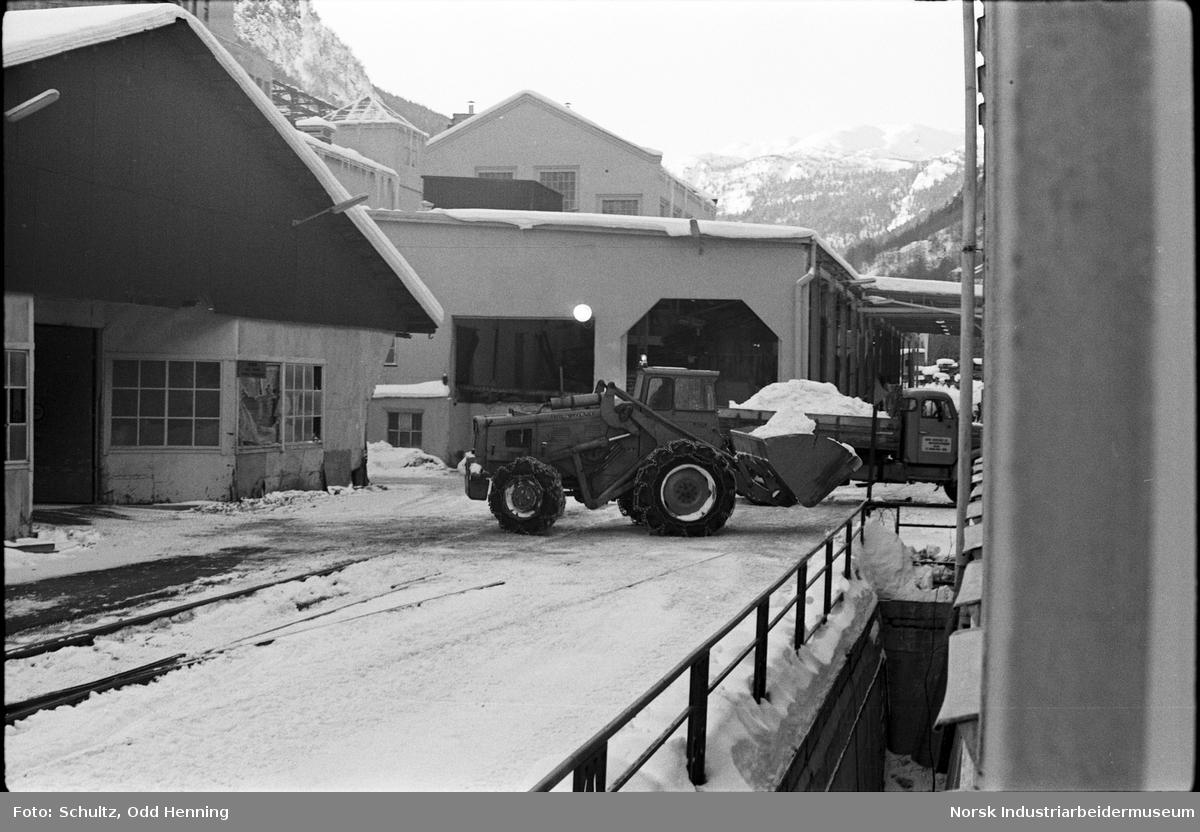 Traktører som rydder snø på fabrikkområde.