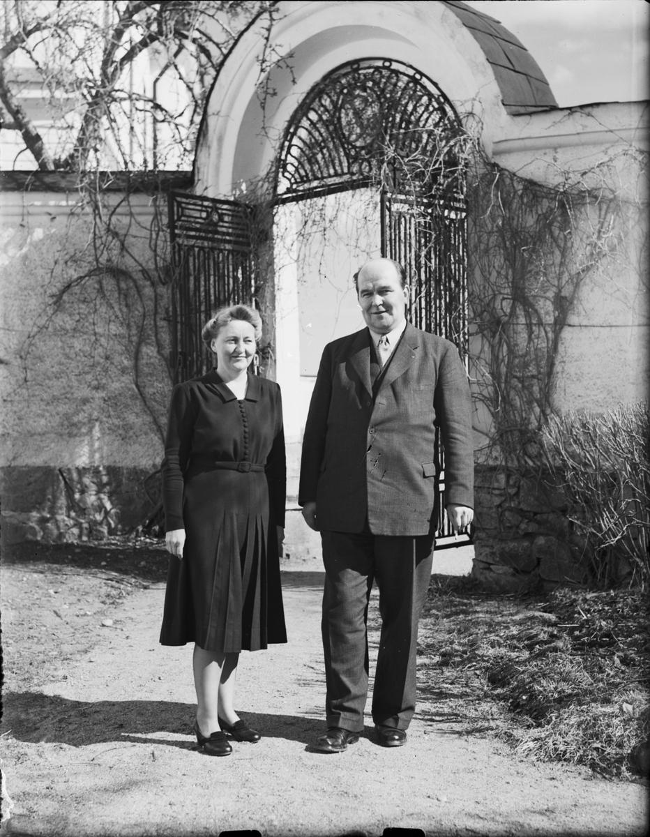 Kvinna och man står på grusgången vid en grind, Gimo, Uppland