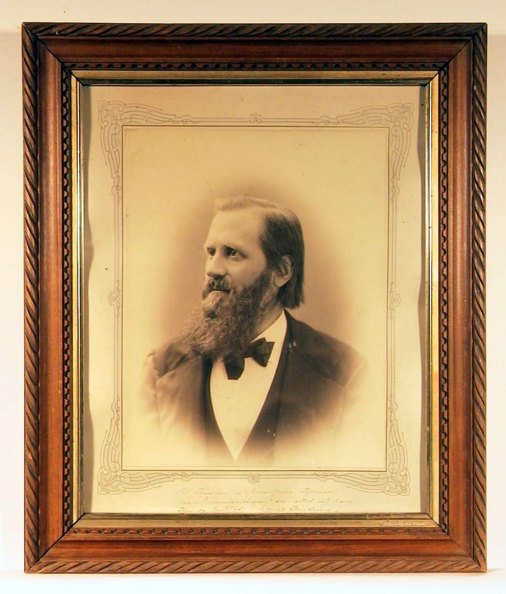 Portrettfotografi i halvprofil av yngre mann med halvlangt hår og langt fullskjegg, kledd i mørk jakke og vest, og hvitt skjorte med butterfly.