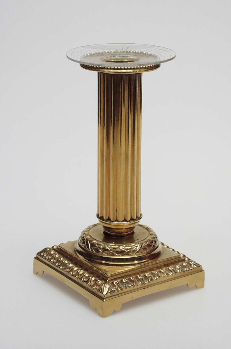 Søyleformet lysestake i messing med kransemotiv på fotstykket. Mansjetten har perlemønster. Lysmansjetten i glass har klassisk mønster. Gjenstanden har preg av empirestil.