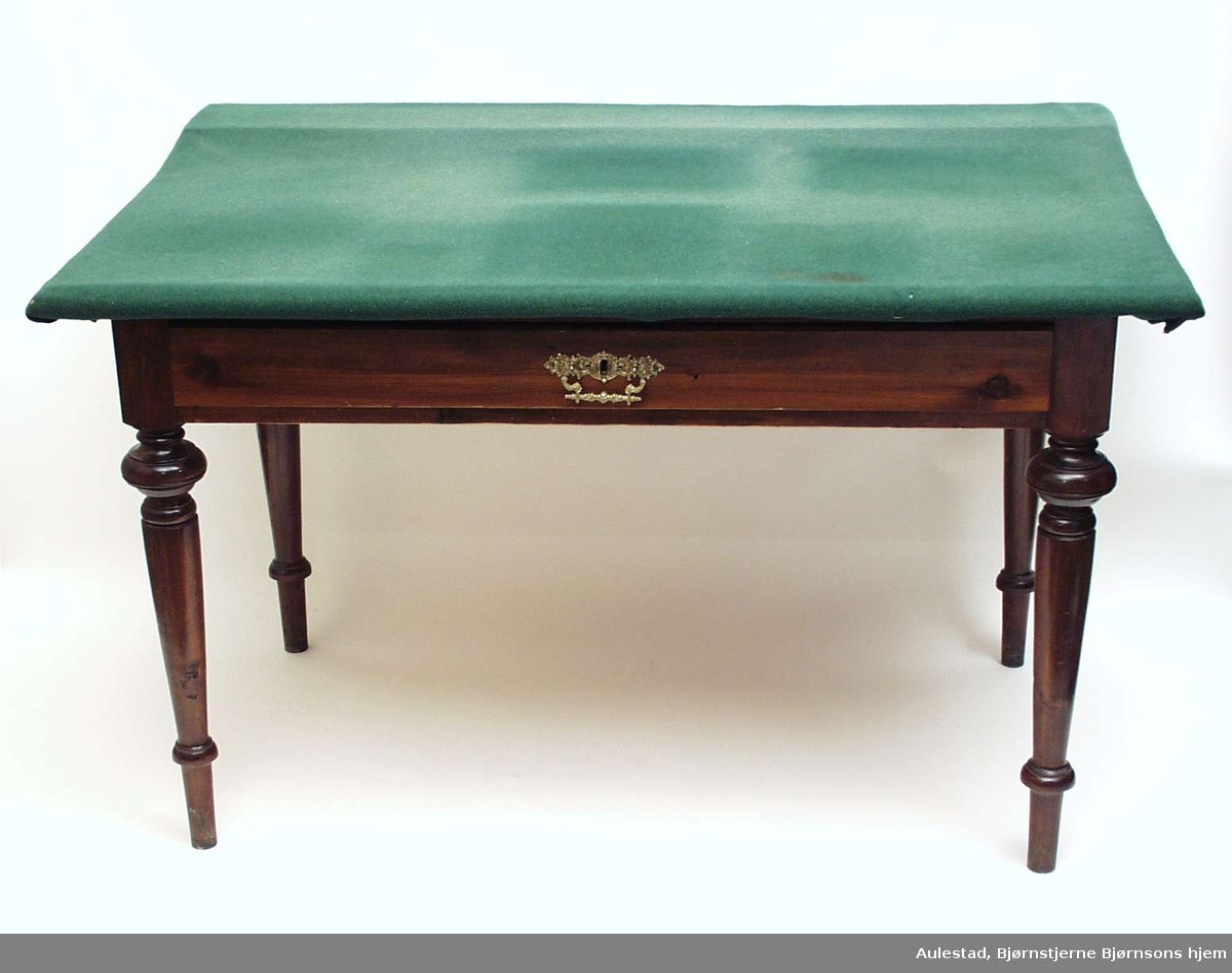 Skrivebord i beiset gran med dreide profilerte ben. Bordet har en skuff med trekkbeslag i sargen. Overplaten har bakstykke og er trukket med grønt tøy. Den opprinnelige bordplaten er 64,5 bred.
