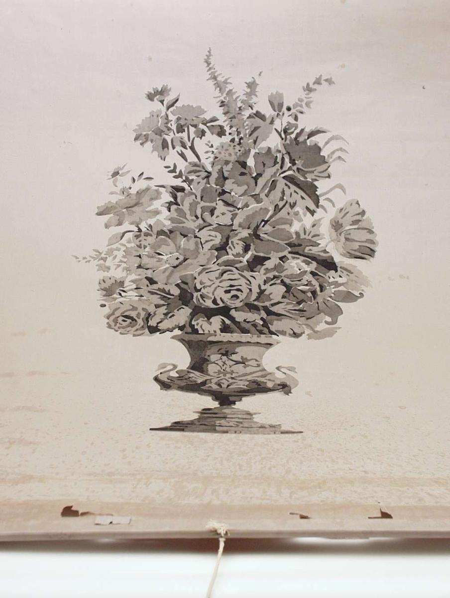 Lys grå rullegardin med motiv i fire gråtoner. Motivet er en urne fylt med blomster, med svaner på sidene. Materialet er impregnert to-skafts bomullstøy. Montert til rundstokk øverst. Innsydd trespile nederst. Påsatt bomullssnor og dreid treknott.