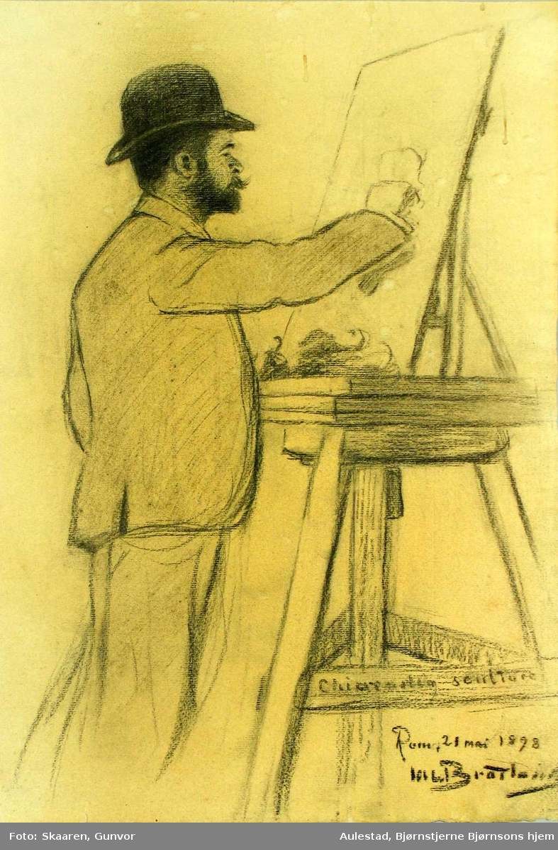 Ung mann med hatt står ved staffeliet og tegner.