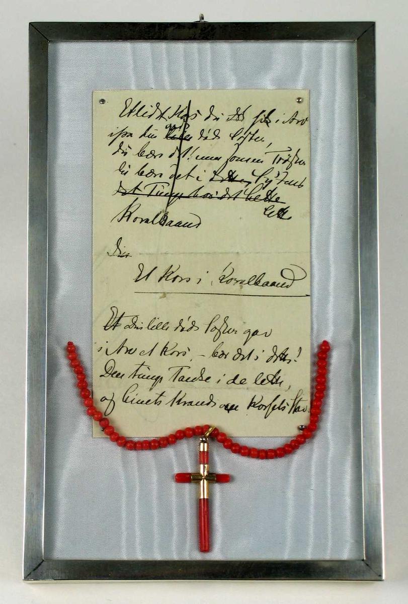 Korallperler med kors festet på hvit silke sammen med diktet. Smykket er satt i glass og sølvramme.
