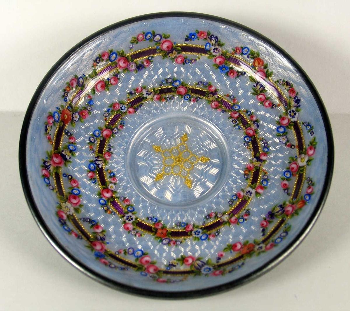 Skål i forsølvet metall og emalje. Den har lys lilla mønstret bunnfarge og to mørk lilla ringer med gullkant. Rundt disse slynger det seg blomsterguirlander. I midten et forgylt ornament.