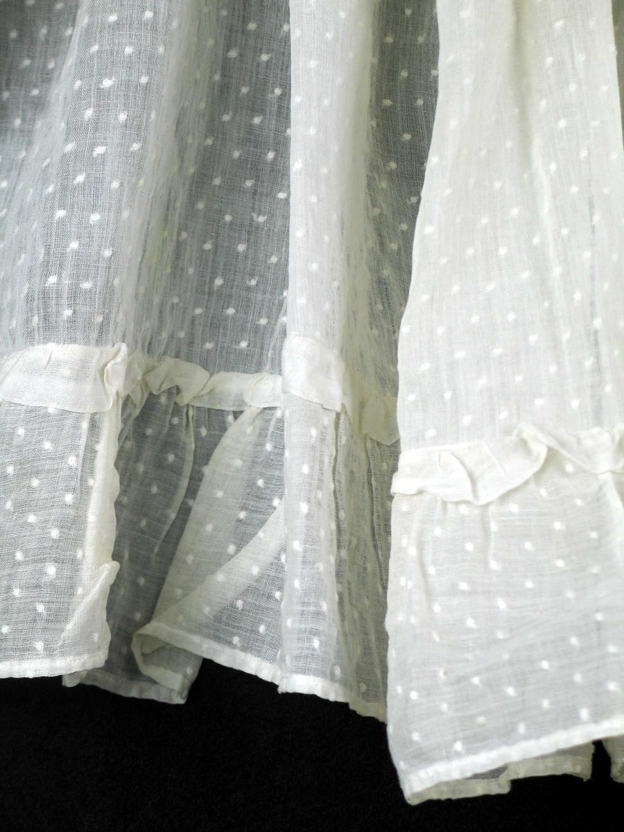 Hvitt forheng i bomull med innvevde prikker. Smal maskinsydd fald på alle sider. Nederst og langs ene siden til 41 cm fra overkant påsydd rynkekappe med rynkehode, 2 cm bred med jarekant.