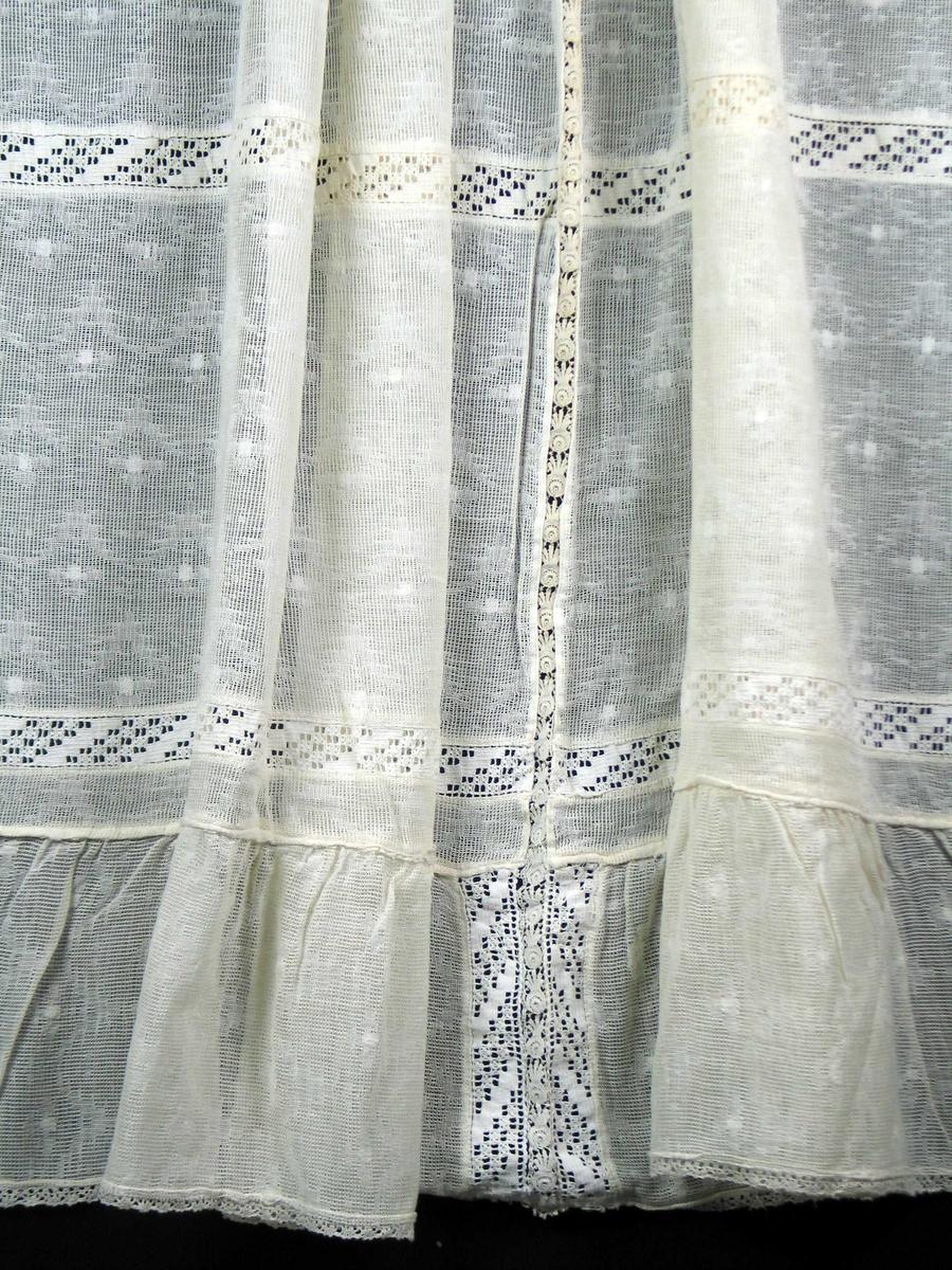 Hvit gardin med innvevd mønster. Stykket er oppdelt i felter med maskintilvirkede border mellom. Rynket kappe nederst med blondekant rundt.