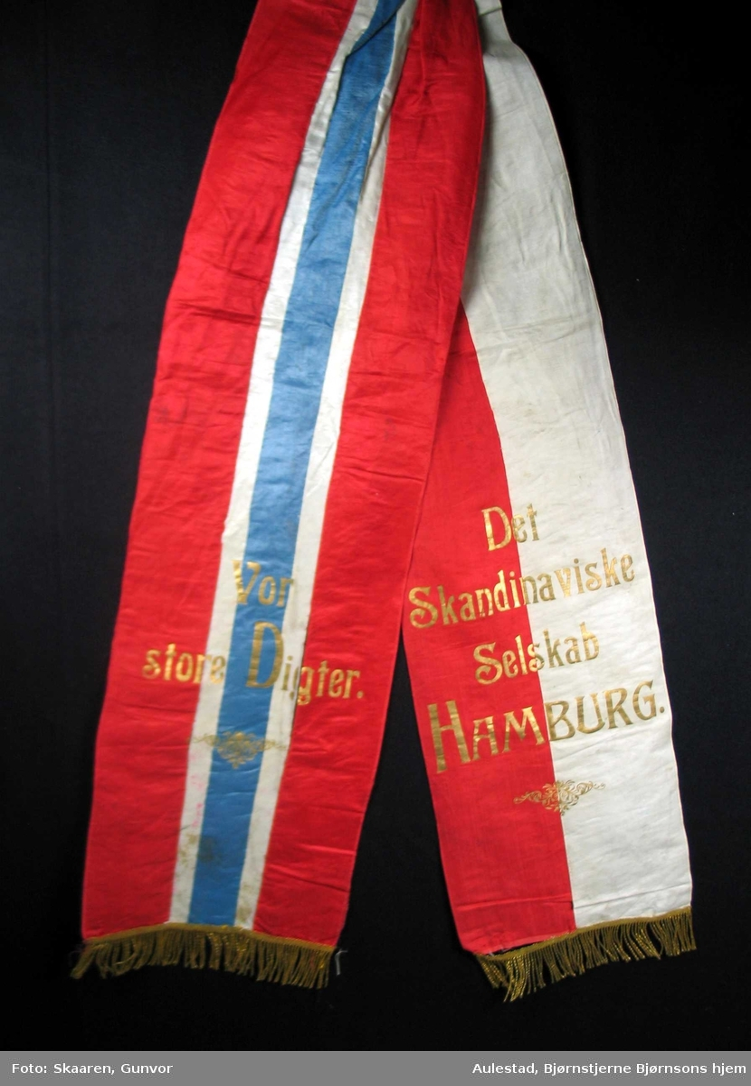 Begravelsessløyfe i rød, hvit og blå silke med frynser og skrift i gull.