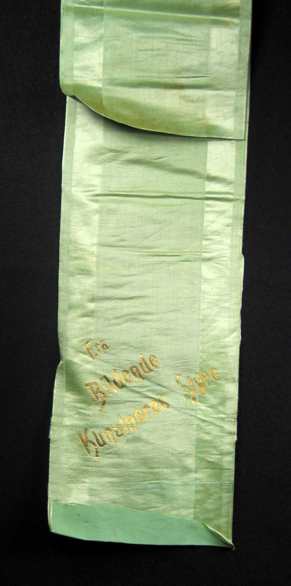 Begravelsessløyfe i grønn silke med tekst i gull.