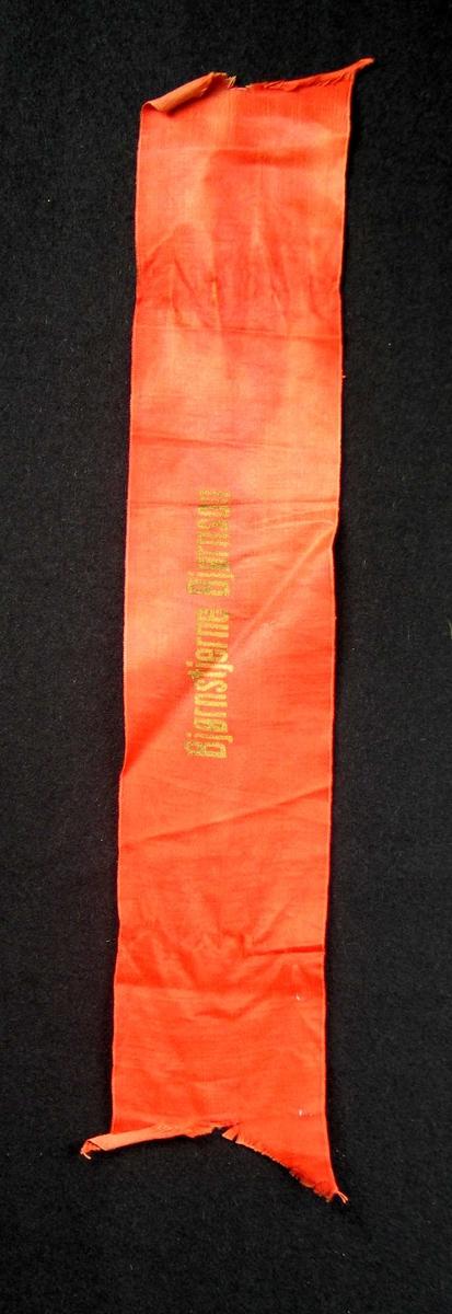 Begravelsessløyfe i rød silke med tekst i gull.