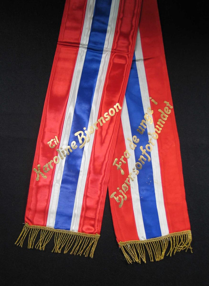 Begravelsessløyfe i rød, hvit og blå silke med tekst og frynser i gull.