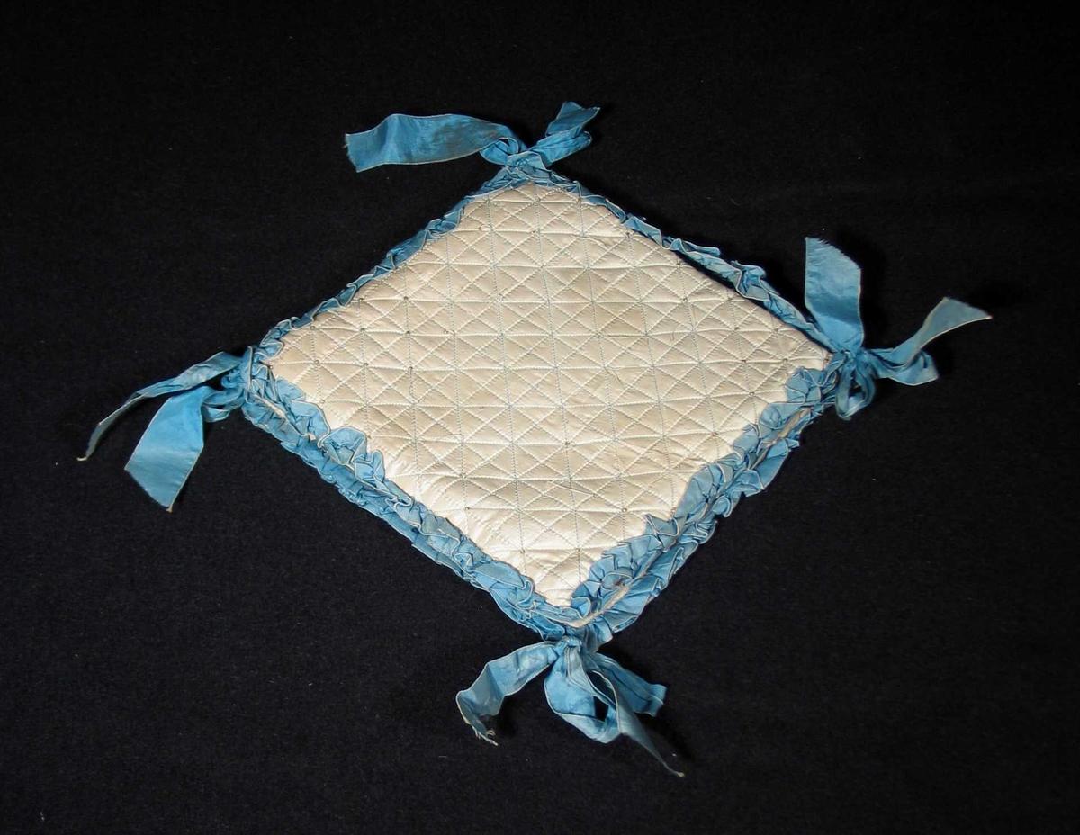 Vattert mappe trukket med lysegrå natursilke. Den har stikninger med påsydde gylne perler.Rundt er det påsydd en rysjekant av blått bånd. Sløyfer i hjørnene holder mappen sammen. Maskinsydd. Perlene er delvis borte.