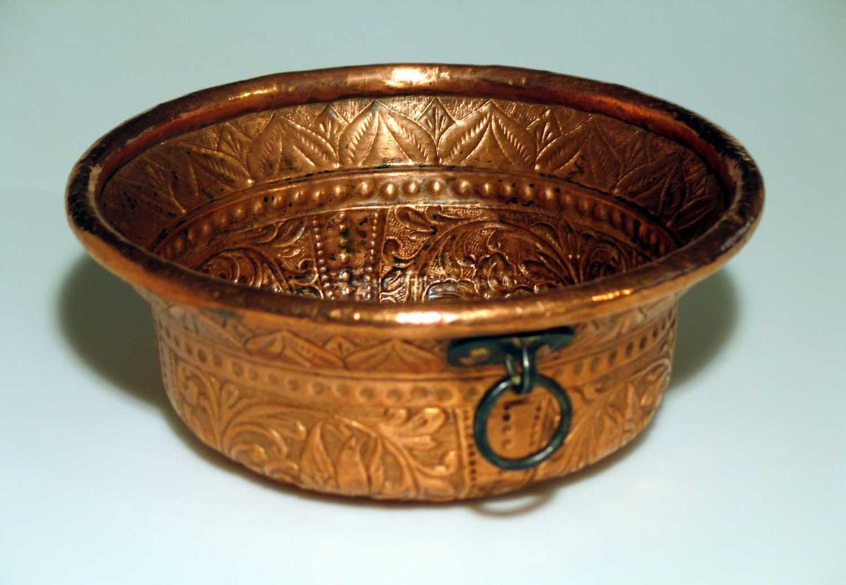 Kobberkar med uthamret blomsterdekor og pånittet hank. I bunnen er motivet tre urner med en krone over.