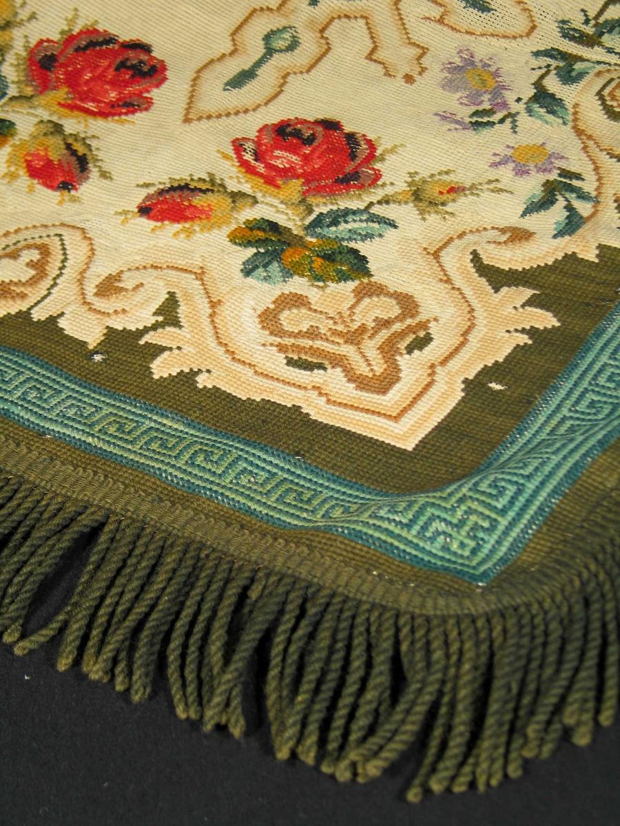 Rektangulært teppe med frynser på alle sider; ytterst á la grequebord i to grønnfarger, lysbrunt/hvitt mønster, kraftige rød roser i hvert hjørne. Trukket med svart forstoff.