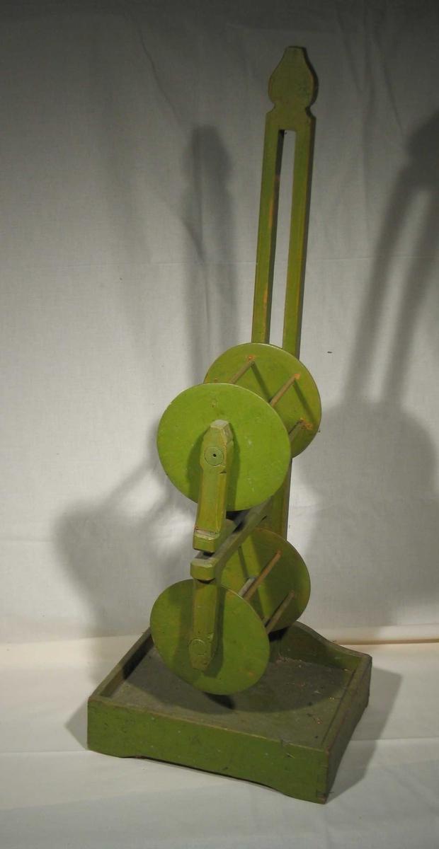Grønnmalt garnvinde i tre med to hjul der det øverste kan justeres i høyden. Rektangulært brett nederst.