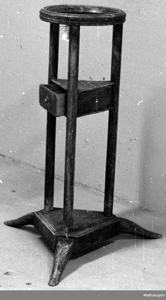Et brunt vaskestativ i tre. Vaskestativet har trekantet fot med tre søyler. På midten har det en trekantet skuffe og øverst en rund ring for fat.